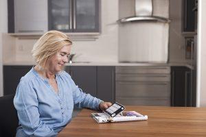 Egy nő az asztalon fekvő folyóiratot olvassa a nagyító segítségével.